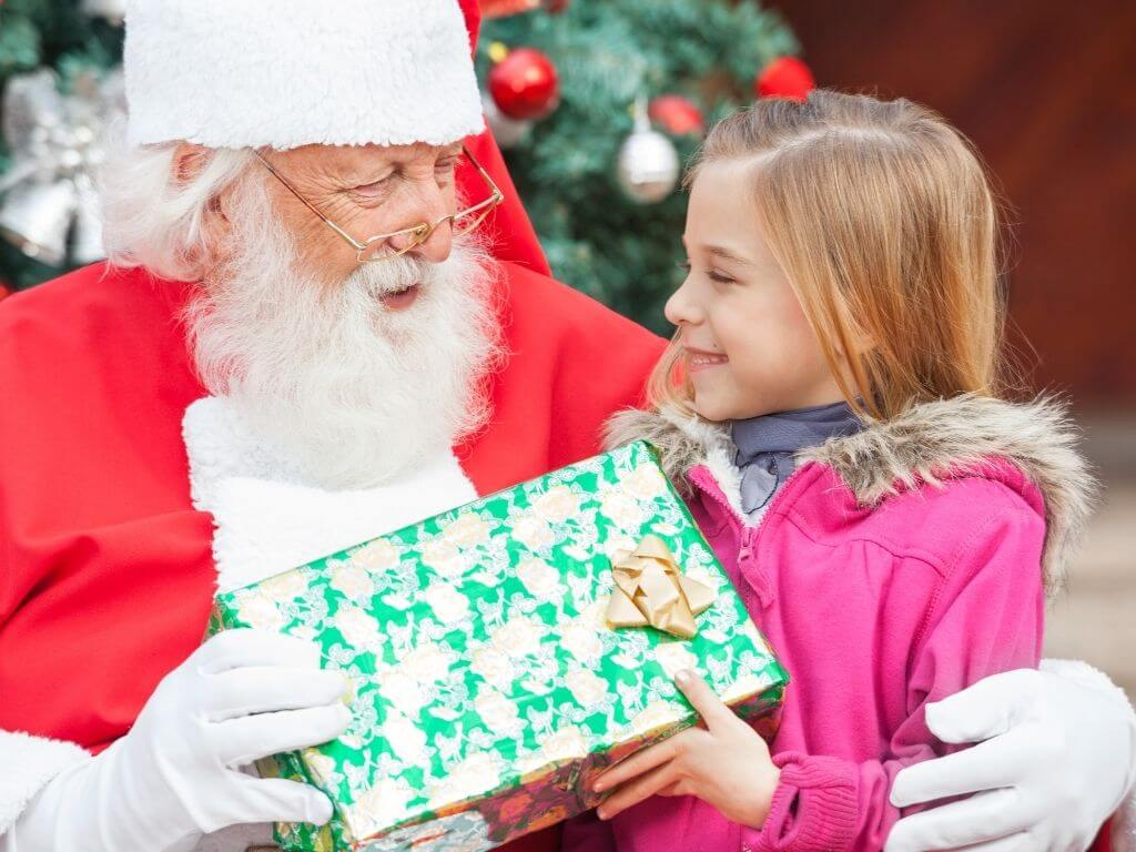 A picture of a girl in a pink coat meeting Santa Claus and receiving a present from him