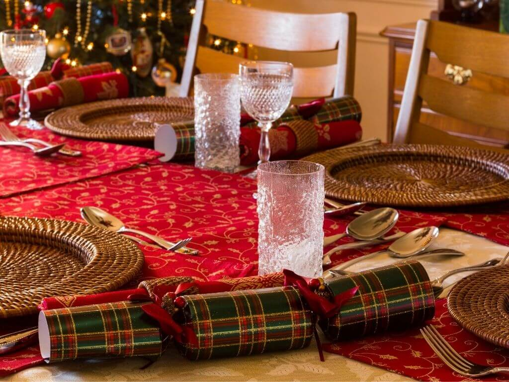 A picture of a Christmas Dinner Table with glasses and Christmas crackers
