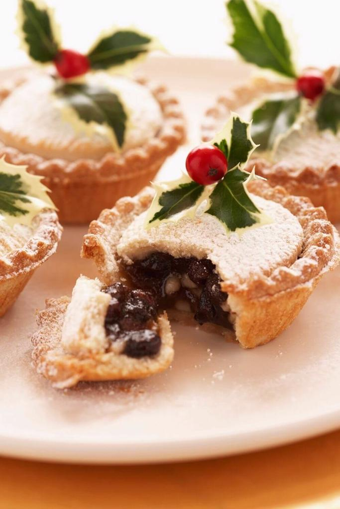 A picture of some festive mince pies decorated with springs of holly