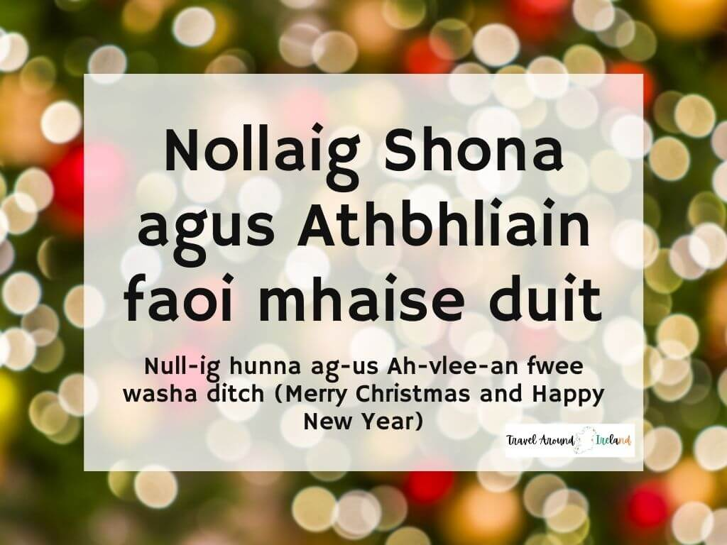 A picture with text over bokeh lights saying Nollaig Shona agus athbhliain faoi mhaise duit meaning Merry Christmas and Happy New Year in Irish