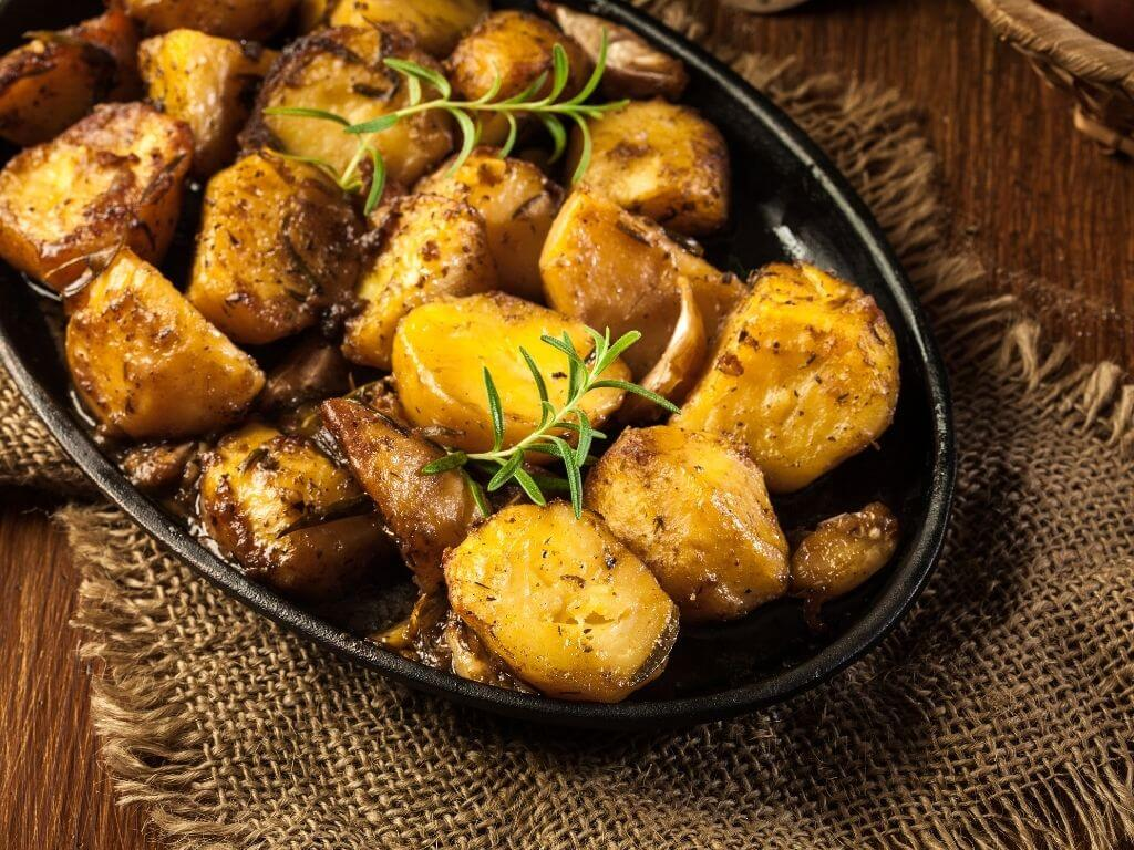 A picture of a roasting dish containing Garlic and Rosemary Roast Potatoes