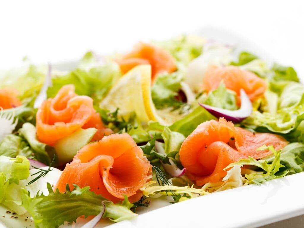 A picture of a bed of lettuce leaves with Smoked Irish Salmon