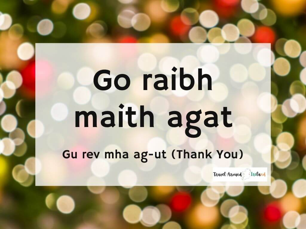 A picture with text over bokeh lights saying Go raibh maith agat meaning Thank you in Irish
