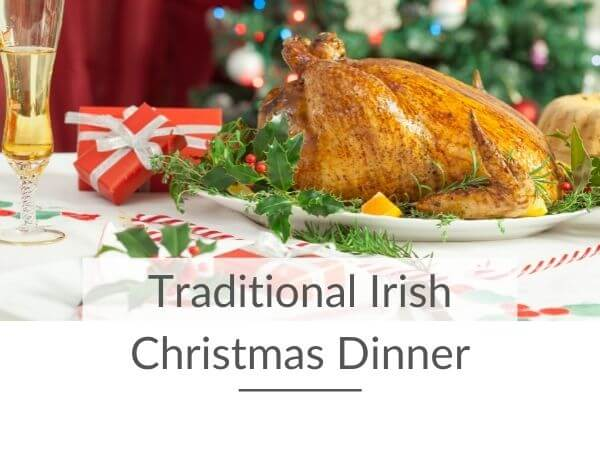 A roast turkey on a plate on a Christmas dinner table with text overlay saying Traditional Irish Christmas Dinner